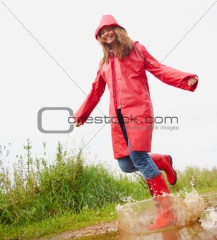 Young female playing in a puddle of water, wearing a red raincoa