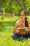 Young woman reading a book outdoors.