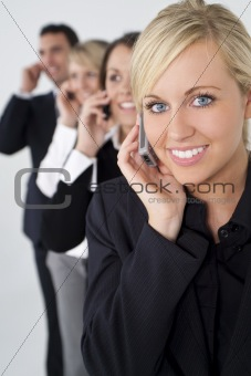 Beautiful Blond Woman On Cell Phone With Team Behind Her