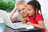 Mixed Race Mother and Daighter Using Laptop Computer At Home