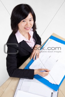 Businesswoman signing document.