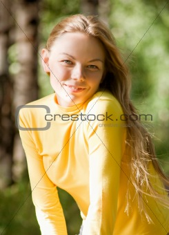 Portrait of a beautiful young woman in summer park