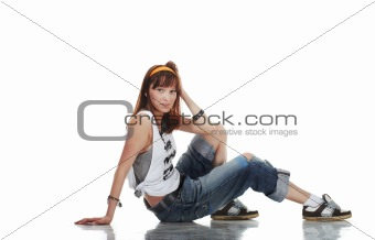 Confused young female dancer sitting on shiny floor on white background