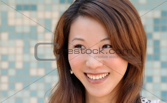 beautiful Asian lady in front of mosaic and smile