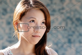 beautiful Asian lady in front of mosaic and watch
