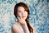 beautiful Asian lady in front of mosaic and think
