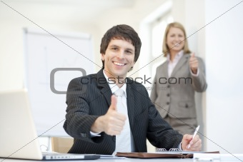 Smart dressed businessman with thumbs uo, teamwork
