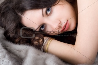 Lovely young woman lying on grey fur coat