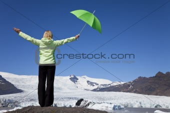 Woman With Green Umbrella In Front Of Melting Glacier