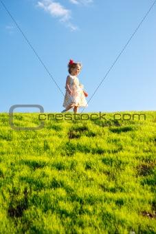 Little girl on a green grass hill