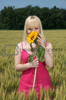 Beautiful blonde girl holding a sunflower