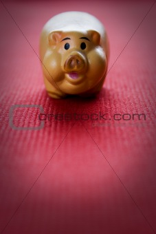 Small clay pig on a red fabric