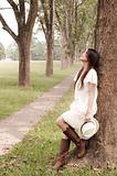 Girl leaning against a tree