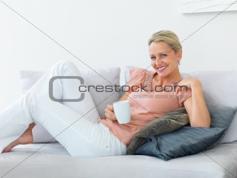 Pretty mature woman having coffee while relaxing at home