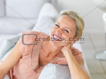 Pretty middle aged woman laughing while sitting on the couch at