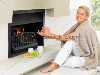 Mature woman smiling by the fireplace