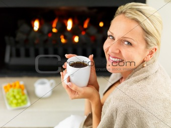 Happy woman having coffee by the fireplace