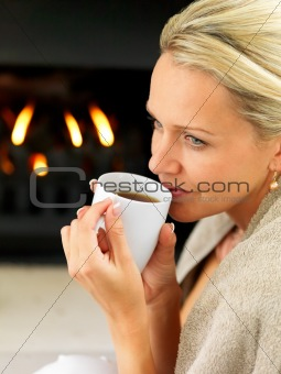 Woman having coffee by a fireplace