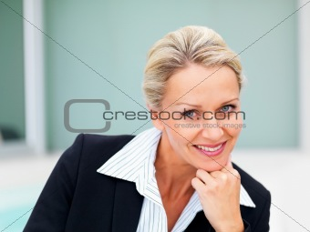 A mature business woman smiling with hand on chin