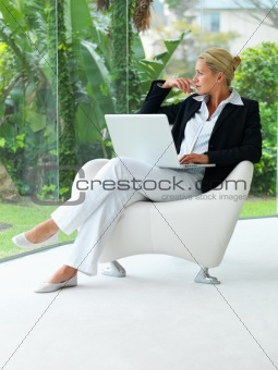 Middle age business woman thinking and looking outside with a la