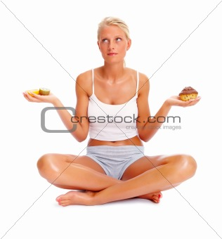 A sexy woman deciding between sweets and fruits over white backg