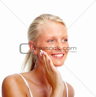 Pretty young girl smiling over white background , touching face