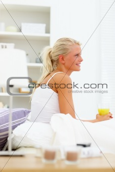 A blond girl drinking juice at home, looking away