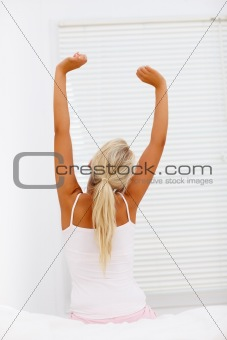 Rear view of tired woman stretching her arms in bed