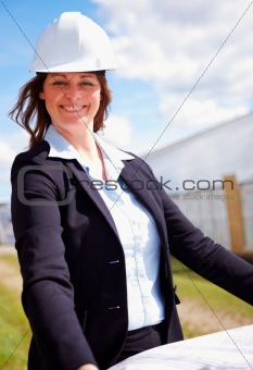 Happy business woman with blue prints at the construction site