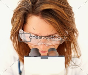Closeup of a young medical scientist working with a microscope