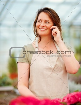 Young florist having a conversation on the mobile at a greenhous