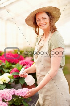 Young female wearing a hat watering the flowers
