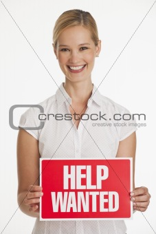 Small business owner holding up Help Wanted sign