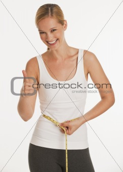 young woman measuring herself and giving thumbs up