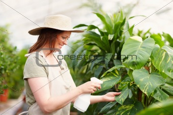 Young female wearing a hat watering the plants