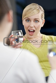 A Surprised Young Blond Woman Drinking With A Friend