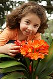 Little girl in a garden of clivia miniata