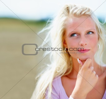 Cute young female in a thoughtful mood while at a field