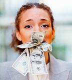 Unhappy young business woman with money in her mouth