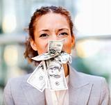 Frustrated young business woman with money stuffed in her mouth