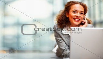Cute young business woman using a laptop on the floor