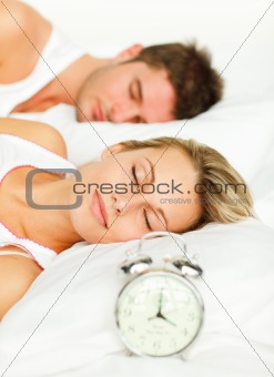 Couple in bed with alarm clock going off