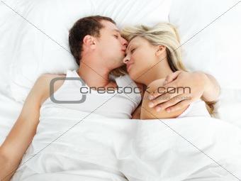 Boyfriend kissing her girlfriend in bed