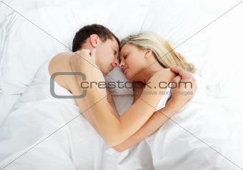 Boyfriend looking at her girlfriend sleeping in bed