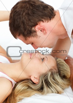 Boyfriend kissing his girlfriend in bed