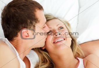 Boyfriend kissing his girlfriend in bed