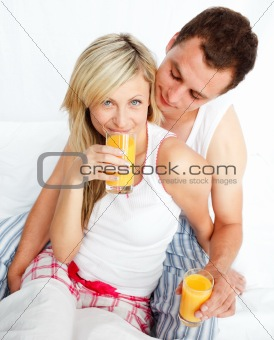 Couple drinking orange juice in bed