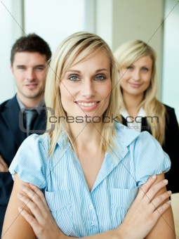 Business people headed by a woman with folded arms