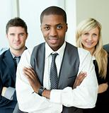 Afro-American businessman with folded arms with his colleagues