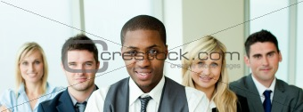 Business team in a row with ethnic manager in the center